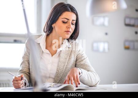 Geschäftsfrau lesen Broschüre während Notizen im Büro - Stockfoto