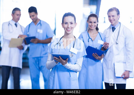 Ärztin mit Tablet und lächelt in die Kamera - Stockfoto