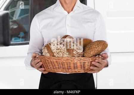 Nahaufnahme eines Bäckers mit einem Korb voller Brot Laib Vor Van - Stockfoto