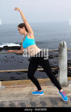 Zierliche Läuferin ausdehnen, indem sie Ballett stellt auf der Promenade - Stockfoto