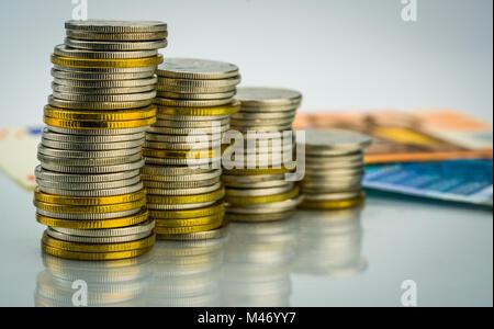 Makroaufnahme Detail des Goldenen und der Silbernen Farbe Münze Stapel mit Banknoten. Business und Finanzen Wachstum, - Stockfoto