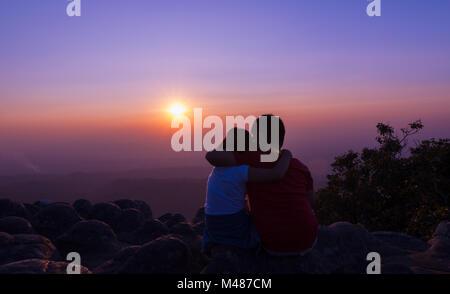 Bruder und Schwester sitzen auf Rock und der Sonnenuntergang am Sunset View Point Hintergrund im Phu Hin Rong Kla National Park Provinz Phitsanulok, Tha siehe
