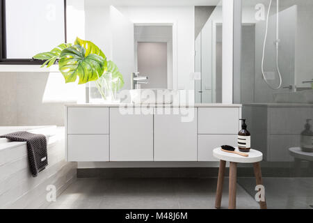 Luxus weißen Familie Badezimmer mit viel Grün und einem hölzernen Hocker styled - Stockfoto