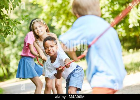 Gruppe von Kindern in Tauziehen Wettbewerb als starkes Team in der Natur - Stockfoto