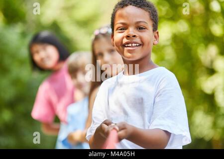 Afrikanischen jungen und multikulturellen Gruppe von Kindern in Tauziehen - Stockfoto