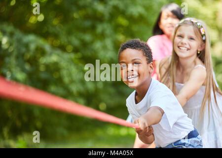 Multikulturelle Gruppe Kinder genießen Tauziehen als Team in der Natur - Stockfoto