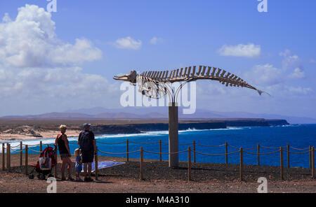 Familie von Touristen beobachtet die Küste von Fuerteventura in der Nähe des Denkmals, bestehend aus einem Wal Skelett - Stockfoto