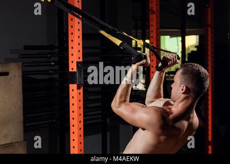 Fröhlicher junger Sportler tun TRX Training in der Turnhalle - Stockfoto