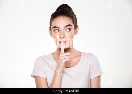 Portrait von schöne nachdenkliche junge Frau mit perfekter Haut holding Zeigefinger auf die Lippen, fragen Schweigen - Stockfoto