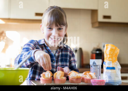 Portrait von Mädchen in der Küche hausgemachte Muffins verzieren - Stockfoto