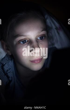 Mädchen mit Handy versteckt unter Bettdecke Nachts im Bett - Stockfoto