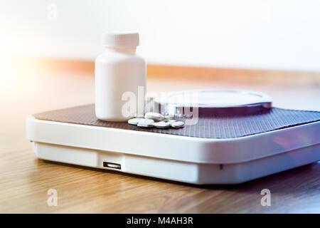 Diätpillen auf einer Skala. Gewicht Verlust Medizin verschüttete aus der Flasche. - Stockfoto