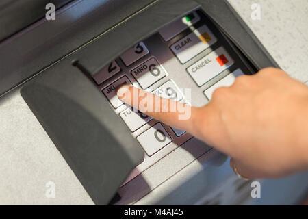 Frau Eingabe Ihrer PIN-Code an Geldautomaten. Geld und Bargeldbezug Konzept. Auf Tasten und Tastatur Hand. - Stockfoto