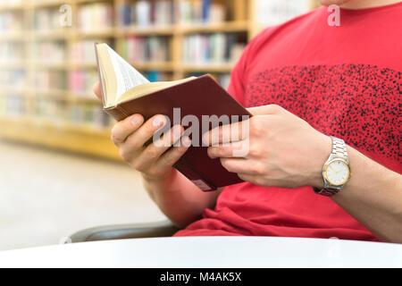Jungen athletischen Mann oder ein Student ein Buch lesen oder in der Schule in der öffentlichen Bibliothek in der - Stockfoto