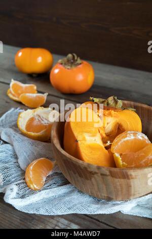 Frische Persimonen und Mandarinen Obst in der Schüssel - Stockfoto