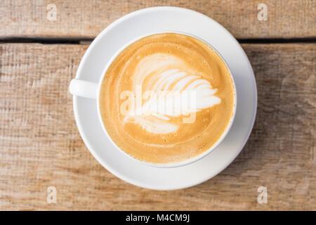 Nahaufnahme einer Tasse Kaffee/Cappuccino mit Schaum und barista Kunst auf Holztisch. - Stockfoto
