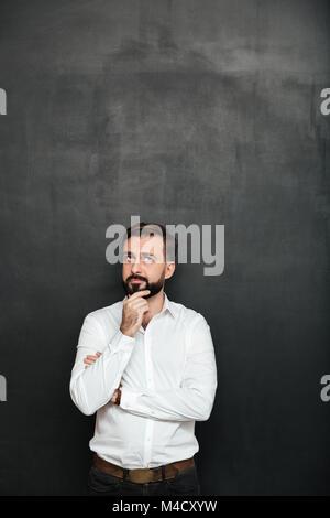 Portrait von brunette bärtiger Mann im weißen Hemd berühren sein Kinn denken oder denken über dunkelgrauen Hintergrund - Stockfoto