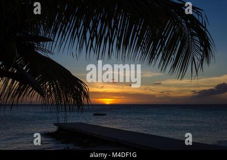 Sonnenuntergang in einem Sandstrand auf einer karibischen Insel - Stockfoto