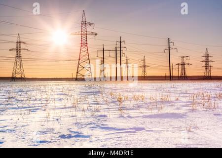 Schönen Sonnenuntergang über einem Feld mit Schnee und vor dem Hintergrund Überlandleitungen abgedeckt - Stockfoto