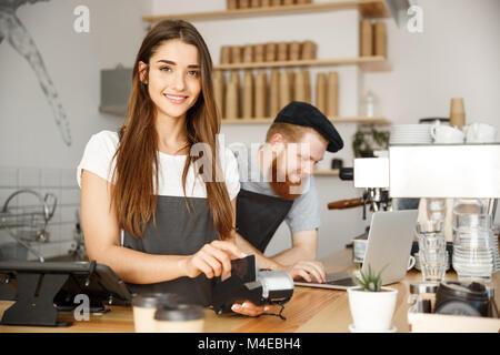 Kaffee Geschäftskonzept - Schöne weibliche Barista, Payment Service für Kunden mit Kreditkarte und lächelnd, während - Stockfoto