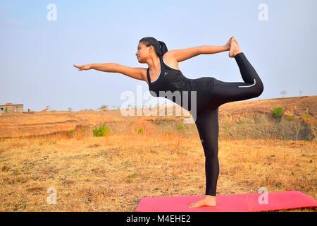 Junge indische Mädchen Yoga. Dandayamana Dhanurasana (Bogen Pose) Ziehen Bergkulisse Pune, Maharashtra. - Stockfoto