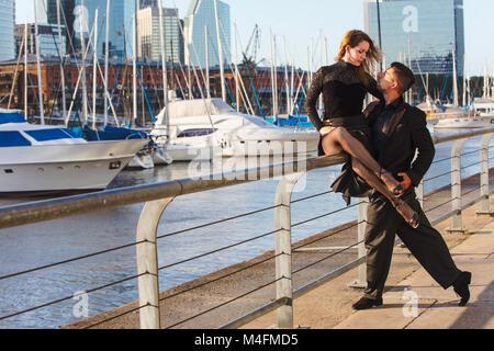 Ein paar Tango tanzen in Puerto Madero, mit Booten in den Hintergrund. Buenos Aires, Argentinien. - Stockfoto