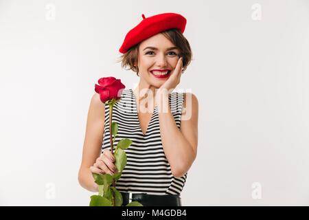 Porträt eines lächelnden Frau das Tragen der roten Baskenmütze Holding eine Rose, und wenn man die Kamera auf weißem - Stockfoto