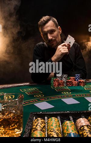 Stattliche poker Spieler mit zwei in den Händen und Chips am Poker Tisch sitzen in einem dunklen Raum voller Zigarettenrauch - Stockfoto