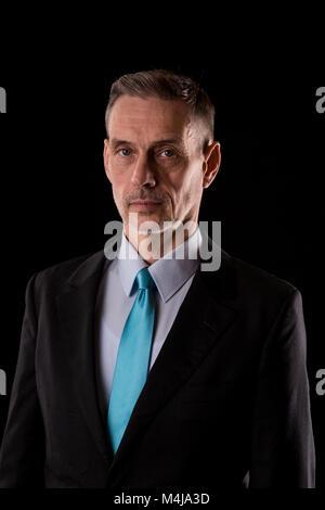 Nahaufnahme der ältere Mann, der in Krawatte über schwarzen Hintergrund. - Stockfoto