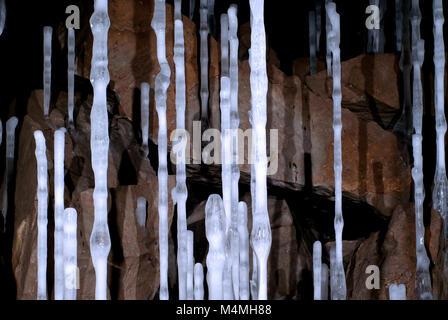 Dünne hohe eisigen Spalten in einer Höhle auf dem Hintergrund der braunen Steine - Stockfoto