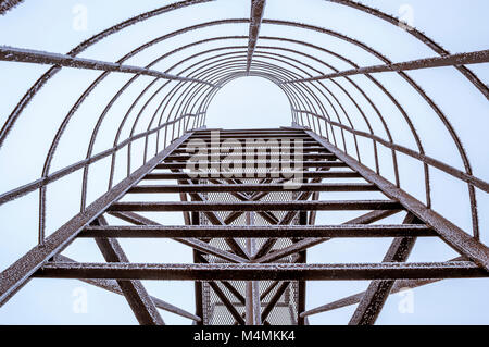 Black Metal Leiter mit Frost bedeckt. Abstrakte Sicht durch die Leiter wie ein Eisenbahntunnel in den Himmel. - Stockfoto