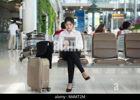 Junge Asiatin Passagier am Flughafen mit ihrem Tablet-PC während des Wartens auf ihrer Flucht im Terminal am Flughafen. Stockfoto