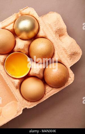 Horizontale closeup Shot mit bunten Karton Behälter mit rosa Farbe mit Huhn Eier, 1 Eigelb, 1 Ei golden bemalt. - Stockfoto