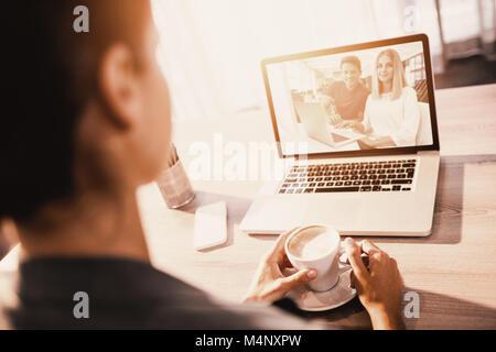 Das zusammengesetzte Bild von Geschäftsleuten über Laptop am Schreibtisch arbeiten in kreativen Büro - Stockfoto
