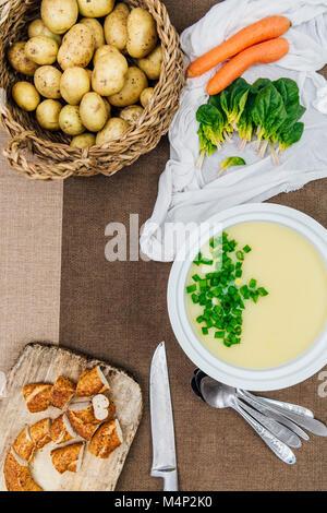 Creme von kartoffelsuppe gekrönt mit gehackten Frühlingszwiebeln in eine weiße Suppentopf aus der Ansicht von oben - Stockfoto