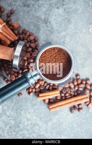 Portafilter close-up mit gemahlenen Kaffee, Sabotage, Zimt und Bohnen auf einem Marmor Hintergrund. Kaffee mit kopieren. Stockfoto