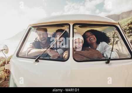 Freunde auf roadtrip Lächeln und Lachen in Van. Gruppe von Mann und Frauen zusammen in einem alten minivan reisen. - Stockfoto