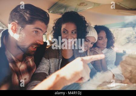 Freunde auf Roadtrip sitzen im Van und mit Karte für die Anreise. Gruppe von Männern und Frauen, die zusammen reisen. - Stockfoto
