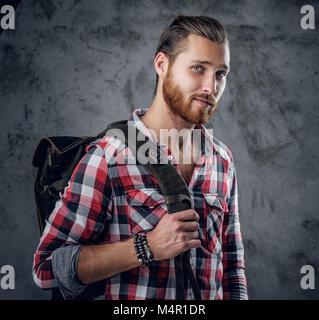 Sanfte bärtigen rothaarige Mann in einem Shirt mit Traveler bag auf seiner Schulter. - Stockfoto