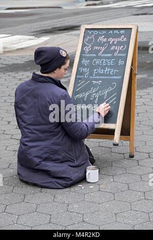 Eine junge Dame in einem wintermantel schreibt ein Zeichen für Bardwell Farm, ein Stand auf der Union Street grünen - Stockfoto