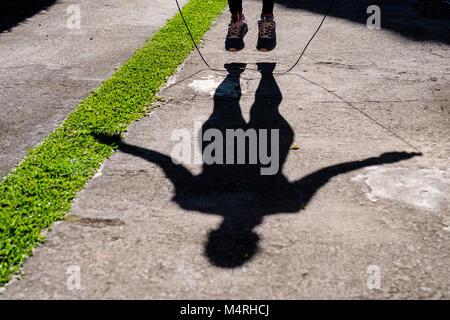 Schatten der passende Frau mit schwarzer Kleidung Seilspringen im Park unter der Sonne, ein gesundes Leben. - Stockfoto