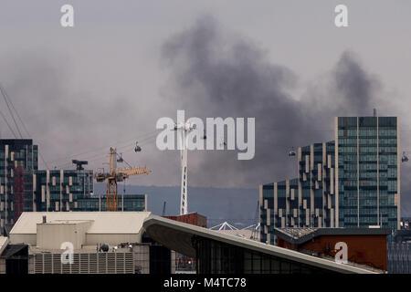 London, Großbritannien. 18 Feb, 2018. London Brand: Schwarzer Rauch steigt über Gebäude aus East London mit Emirates - Stockfoto