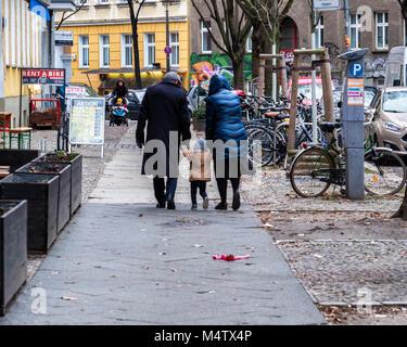 Berlin, Prenzlauer Berg. Mann, Frau und Kind in warmen Winter Mäntel gehen auf Pflaster. Street Scene - Paar und - Stockfoto