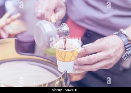 Nahaufnahmen der Hände des Menschen die traditionellen türkischen Kaffee in Kupfer Turk auf heißem Sand, gießt in - Stockfoto