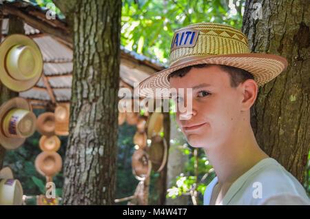 Labadee, Haiti. Porträt einer teenaged Jungen tragen ein handcrafted straw hat vor dem Hintergrund der Bäume und - Stockfoto