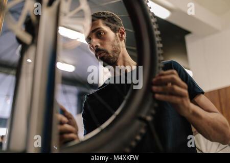 Arbeitnehmer Ausrichten eines Fahrrades in der Werkstatt. Mann bei der Arbeit auf einem Fahrrad in eine Werkstatt. - Stockfoto