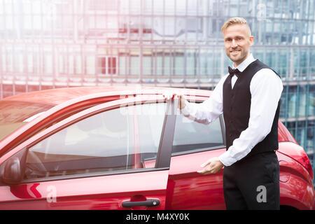 Porträt von einem gutaussehenden jungen männlichen Valet Öffnen rotes Auto Tür - Stockfoto