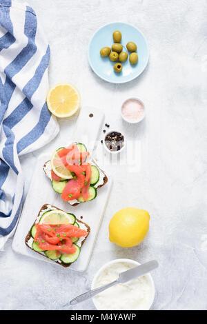 Sandwiches mit Lachs, Gurke und Frischkäse auf weißem Hintergrund. Ansicht von oben. Mediterrane Küche - Stockfoto