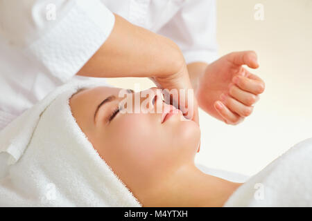 Schöne Frau an eine Gesichtsmassage in einem Spa Salon - Stockfoto