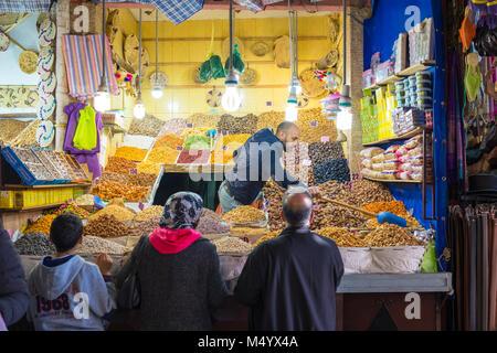 Kunden Prüfung getrocknete Ware von beleuchteten Markt bei Dämmerung, Marrakesch, Marokko Marrakesh-Safi ausgeht, - Stockfoto